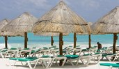 A tourist sits among empty beach chairs in Cancun, Mexico